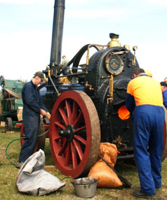IN MOTION: Club members Michael Crossen and Brian Rhodes keep a 1870 Hornsby portable steam engine in steam.