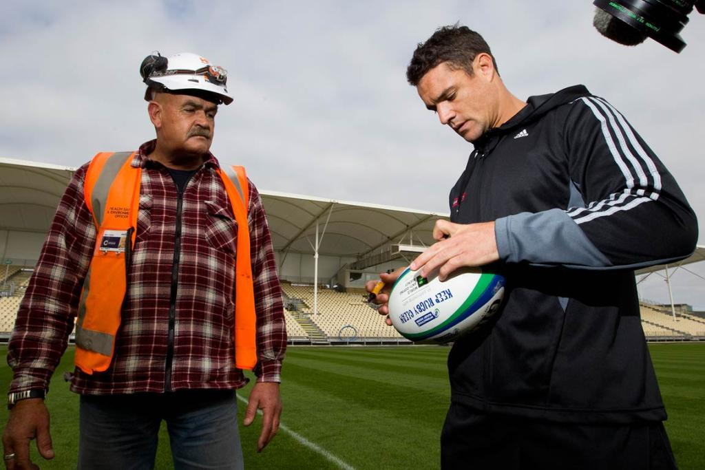 Dan Carter signs a rugby ball for Bruce Hodge, health, safety and environment manager at the Christchurch Stadium site.