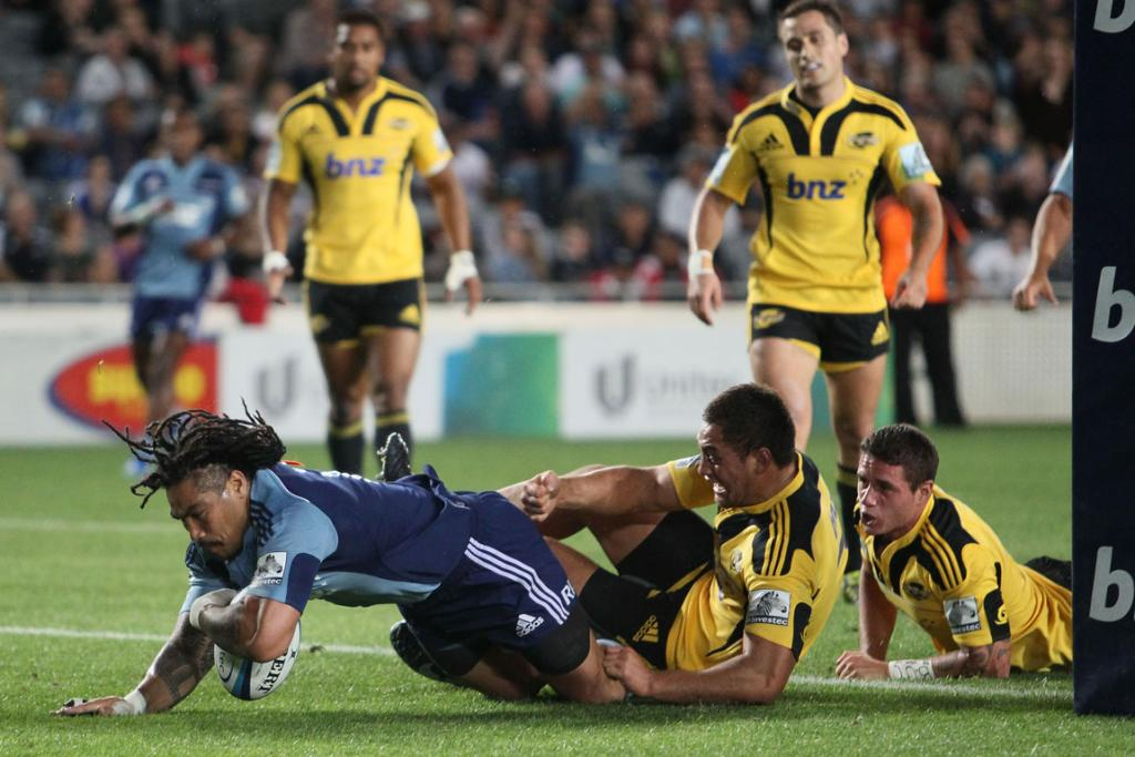 Blues second five eighth Ma'a Nonu dives over to score in the tackle of Hurricanes flanker Jack Lam.