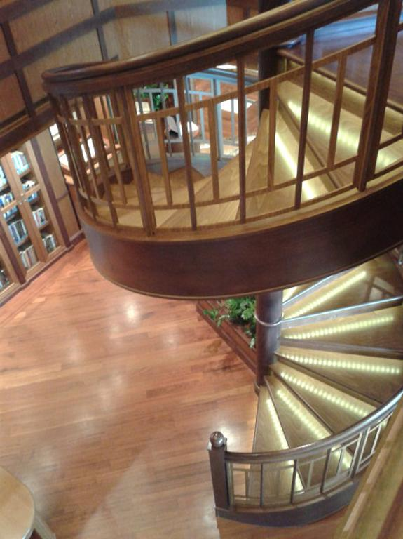 A spiral staircase connects the two floors of the library.