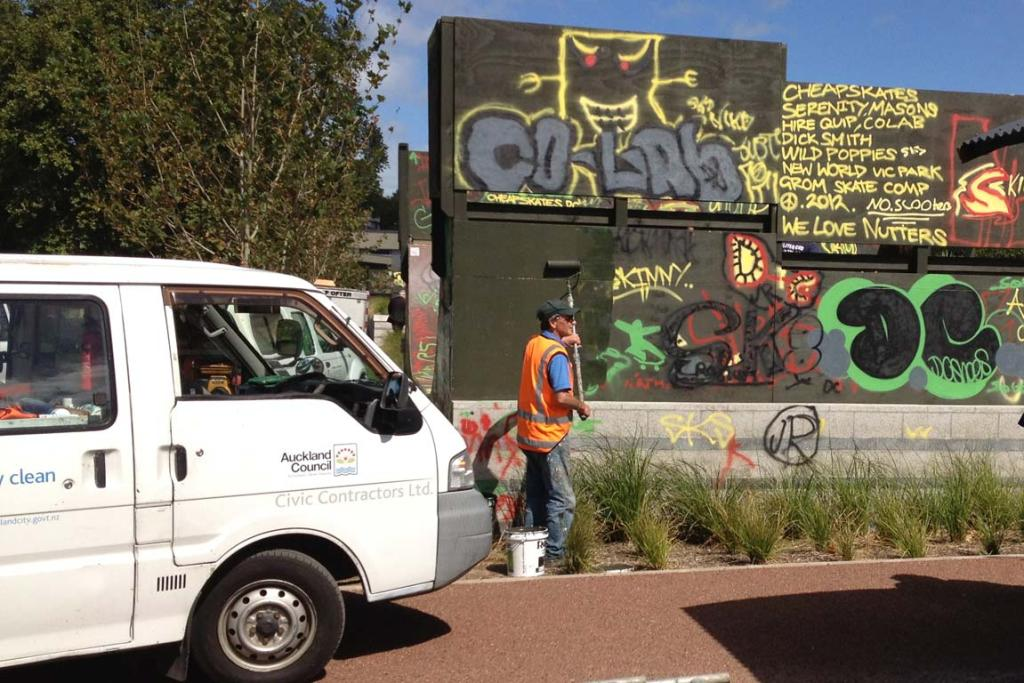 An Auckland Council contractor begins painting over the vandalised Victoria Park skate park.