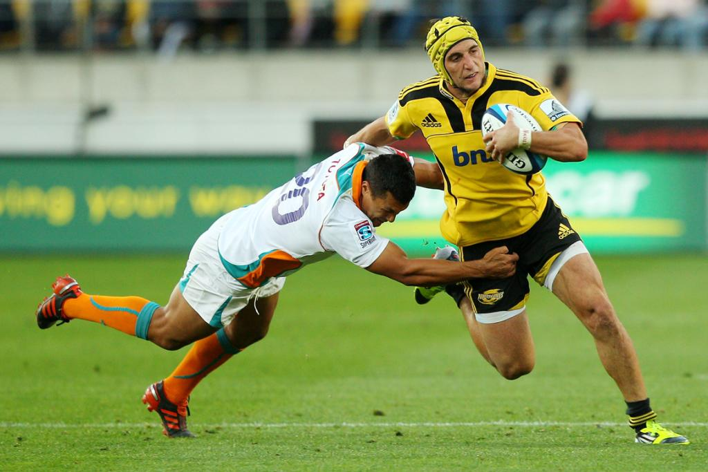 Andre Taylor (right) of the Hurricanes is tackled by Tewis de Bruyn of the Cheetahs.