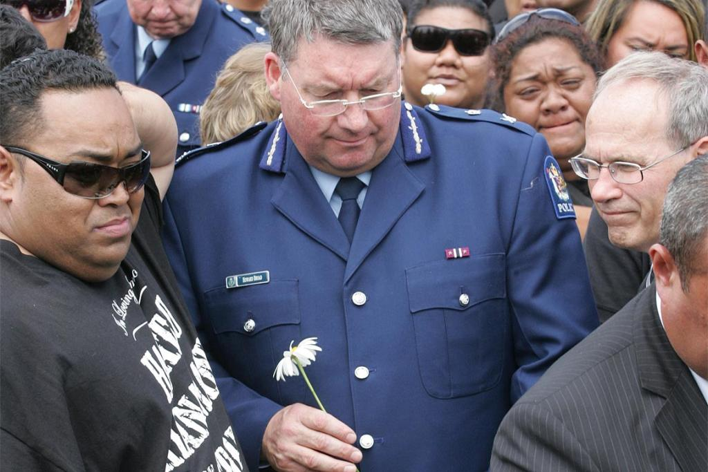 Police Commissioner Howard Broad and then-Manukau mayor Len Brown by the graveside at the funeral Halatau Naitoko.