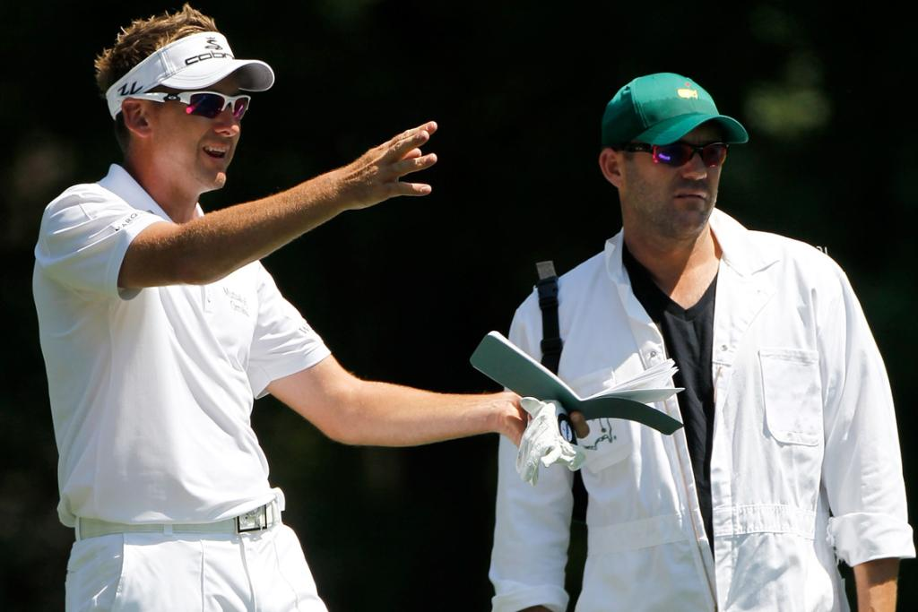 Ian Poulter (L) of England talks with his caddie Terry Mundy during a practice round.