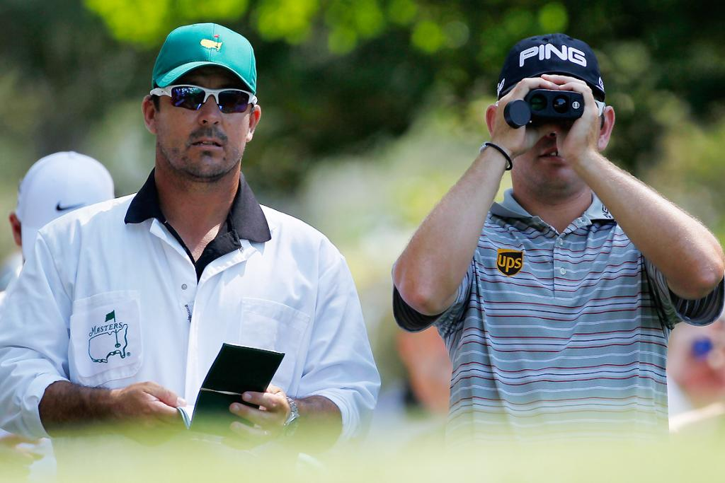 Louis Oosthuizen of South Africa looks at a shot with his caddie Wynand Stander during a practice round.