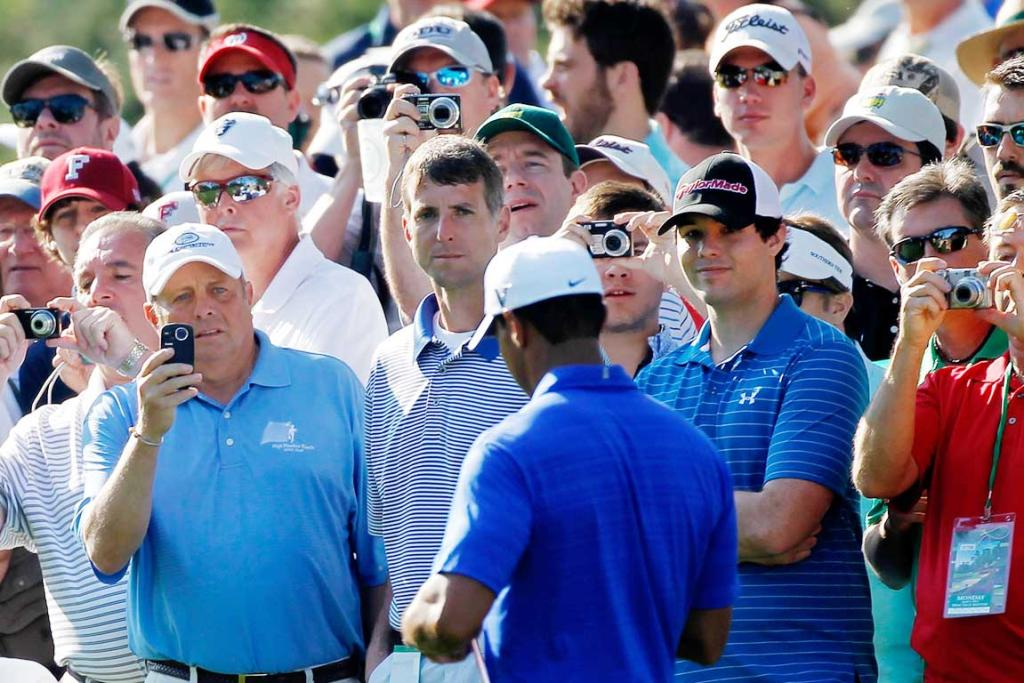 Spectators take photos of Tiger Woods during a practice round.