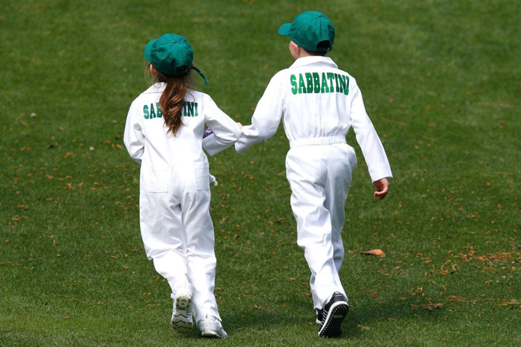 Two children of South African golfer Rory Sabbatini run up the fairway during the pre-US Masters par-three tournament.