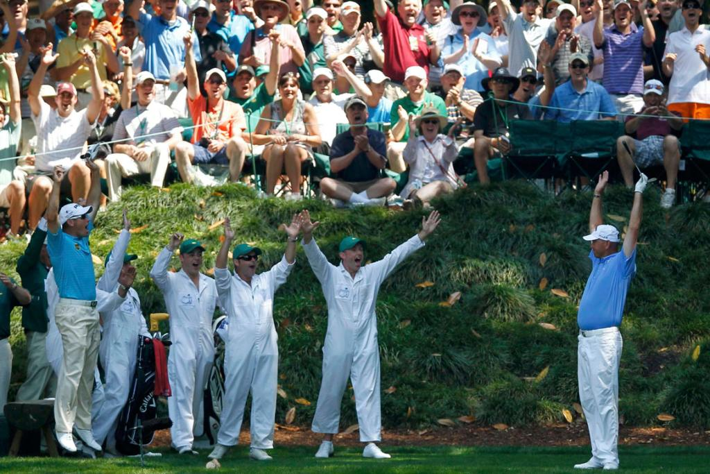 Thomas Bjorn (R) and entourage celebrate the Danish golfer's hole-in-one on the ninth hole of the pre-US Masters par-three tournament.