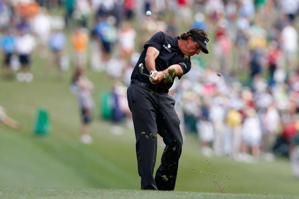 Phil Mickelson hits his approach shot to the green on the first hole.