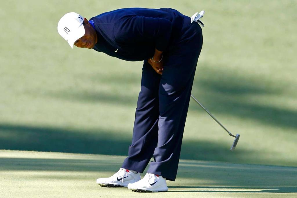 Tiger Woods uses some body english to try to coax a putt to move the way he wants.