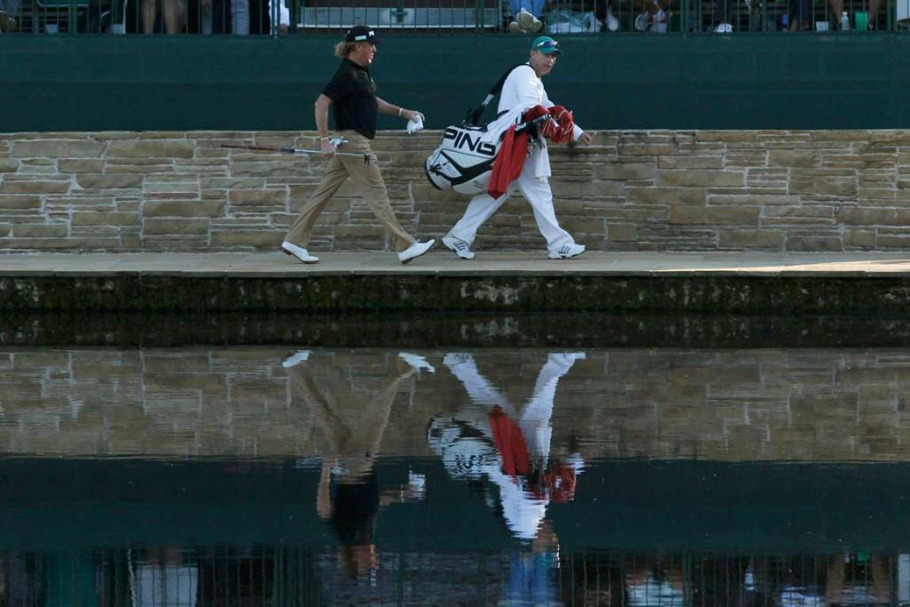 Miguel Angel Jiminez and his caddie Pascual Jiminez walk past the water on the way to the 15th green.
