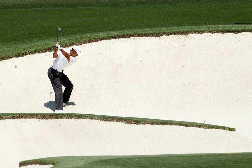 Tiger Woods chips out of the bunker in front of the eighth green during his even par third round.