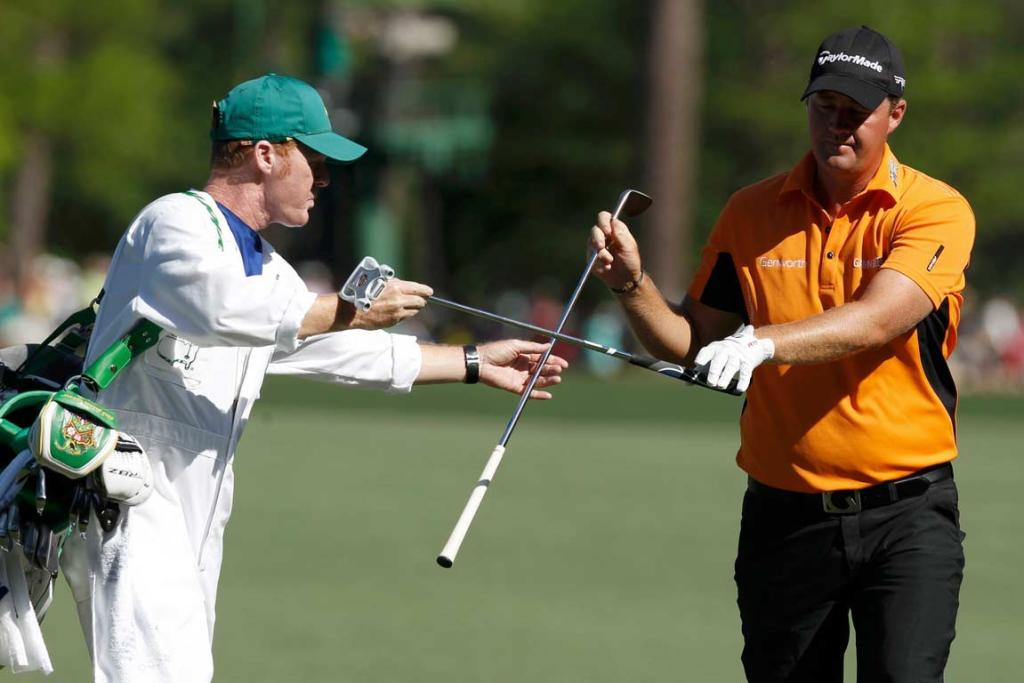 Leader Peter Hanson exchanges clubs with his caddie during the third round.
