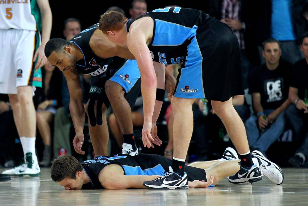 Tom Abercrombie lies on the court in agony after severely straining ligaments in his left ankle.
