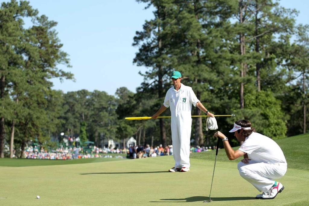 Bubba Watson of the United States lines up a putt as caddie Ted Scott looks on during the final round.
