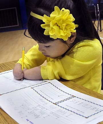 Annie Clark, a first-grade student at Wilson Christian Academy in the US who was born without hands or lower arms, demonstrates how she writes in a booklet.