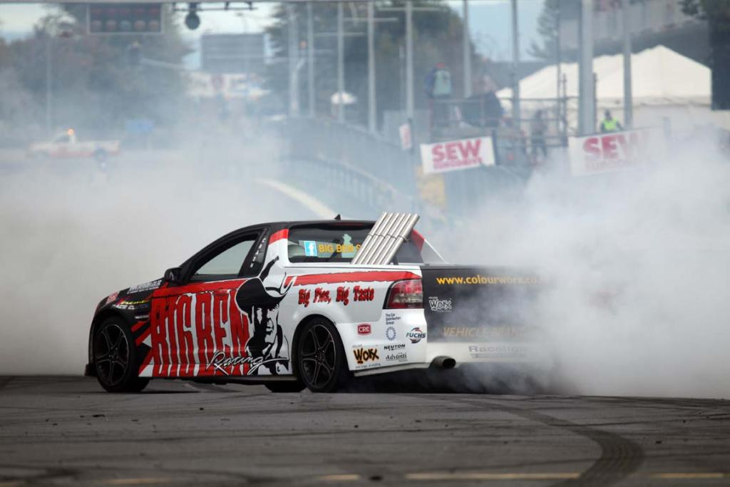 A V8 ute does a burnout demonstration on practice day.