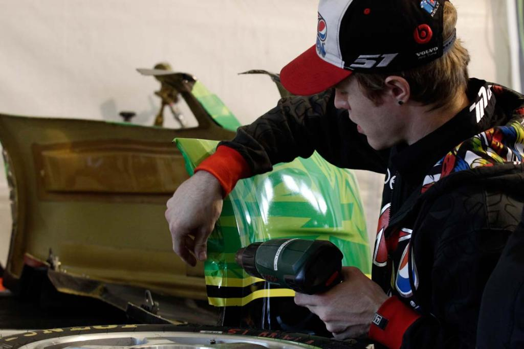 A crew member works on repairs to Greg Murphy's front bumper.