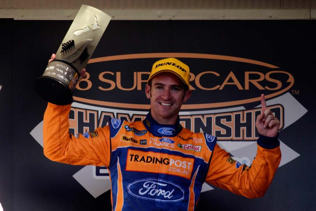 Will Davison celebrates on the podium after his race one victory.