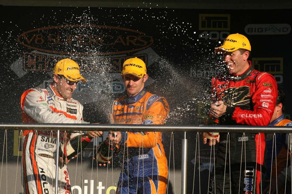 Hamilton 400 race one winner Will Davison sprays champagne on the podium with Jamie Whincup (left) and Garth Tander (right).
