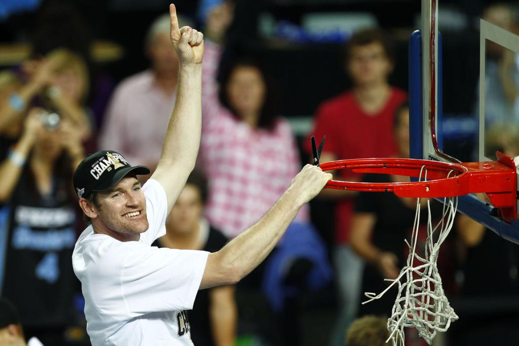 New Zealand Breakers' Dillon Boucher participates in the championship-winning tradition of cutting down the nets.