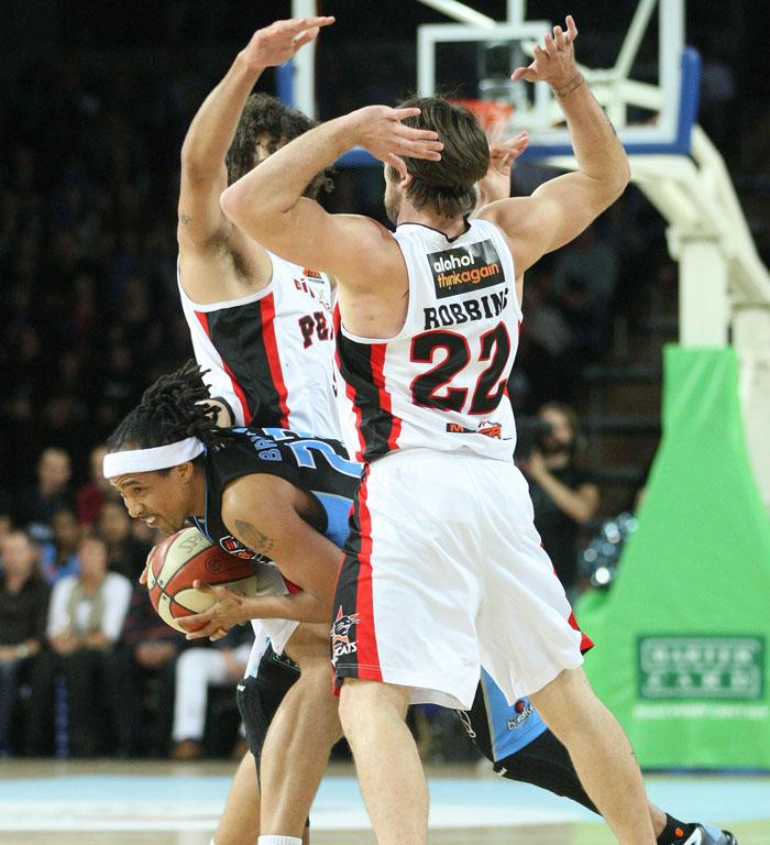 CJ Bruton of the Breakers ducks through the arms of Matt Knight and Brad Robbins of the Perth Wildcats.