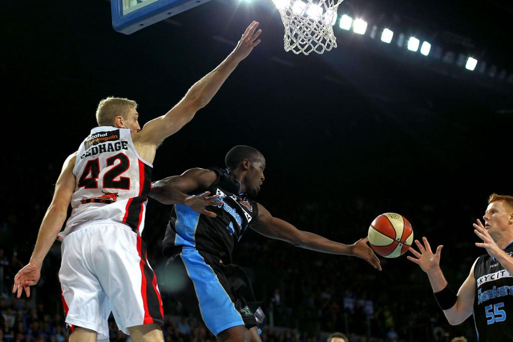 Cedric Jackson delivers the ball to centre Gary Wilkinson as Perth's Shawn Redhage attempts a block.