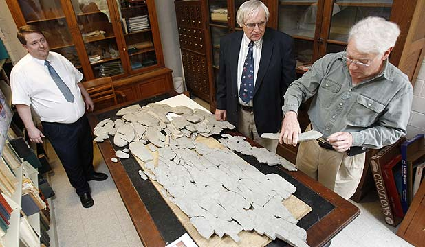 Amateur paleontologist Ron Fine discusses the fossil he discovered with Carl Brett (centre) and David Meyer, professors of Geology at the University of Cincinnati, at Caster Library on the campus in Cincinnati.