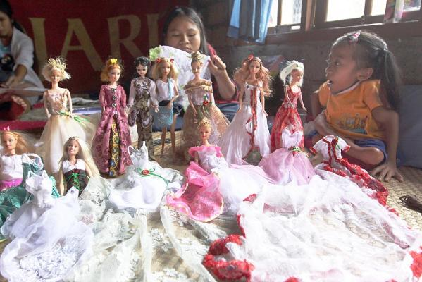Sisters Alit Astini (right) and Putu Restiti display Barbie dolls at their house in Songan village, Kintamani, Bali, Indonesia.