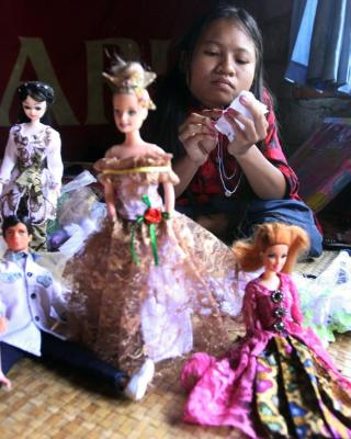 Putu Restiti  stitches Barbie dolls dress at her house i n Songan village, Kintamani, Bali, Indonesia.
