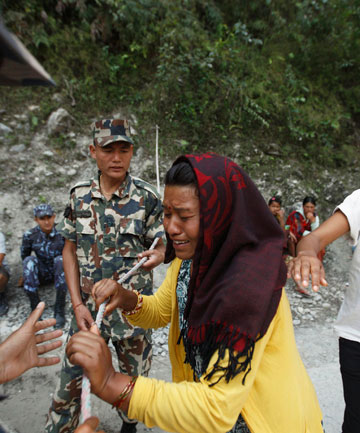 A woman, whose daughter is missing, cries near an area, swept away by a flood caused by an avalanche in the Annapurna mountain range in Nepal's Kaski district.