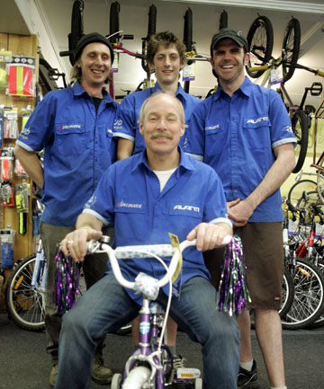 TRAINER WHEELS: Jim Matthews rides one of the big bikes watched by his staff at Village Cycles.