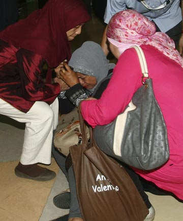 A relative weeps upon inspecting the list of passengers on board a missing Russian airplane at Halim Perdanakusuma Airport in Jakarta, Indonesia.