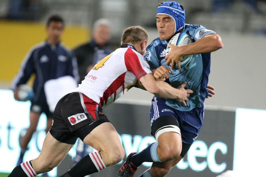 Blues wing Benson Stanley is tackled by Lions wing Deon Van Rensburg.