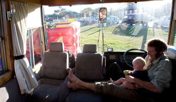 ON THE ROAD: Paul and Debi Ogilvie quit their jobs and packed up their lives to join the Gypsy Fair. Paul relaxes inside the house bus with baby Hope, aged 8 months.