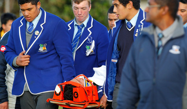 Jayden Hinaki is carried from the field  to a waiting ambulance by his schoolmates.
