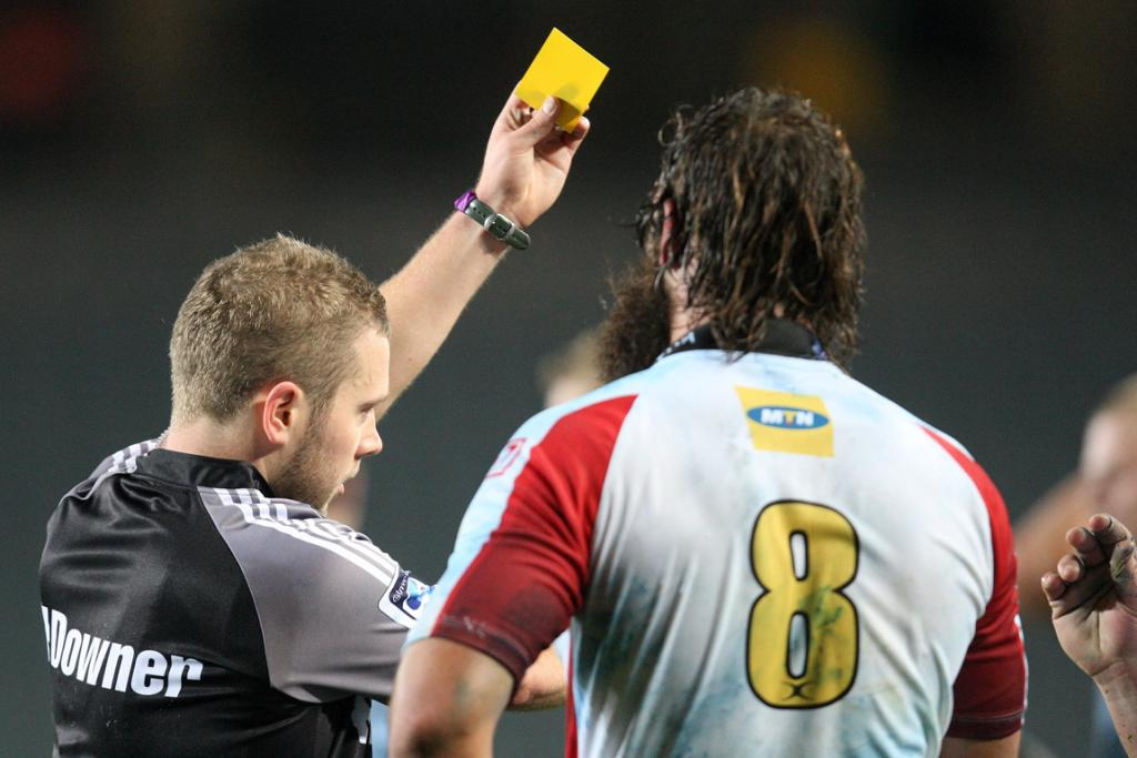 Referee Angus Gardner issues a yellow card to Deon van Rensburg of the Lions.