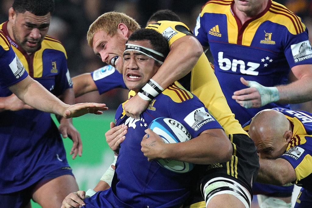 Nasi Manu of the Highlanders is tackled against the Hurricanes.
