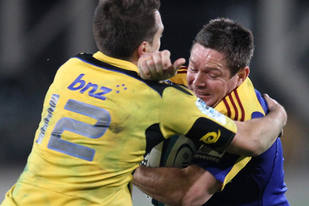 Mike Delany of the Highlanders is tackled by Tim Bateman of the Hurricanes.