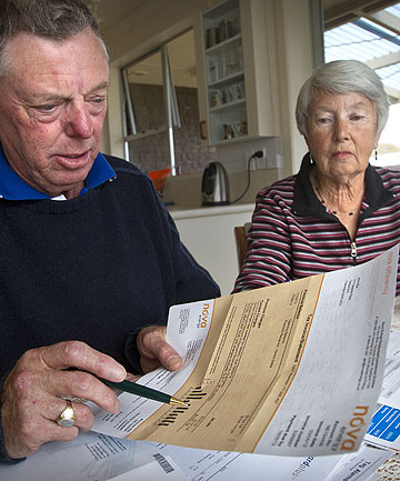 STRUGGLE: Gary and Janis Muir check their bills. Falling interest rates mean they now have less disposable income.