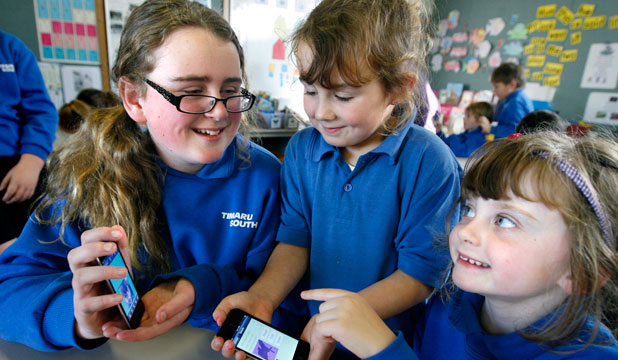Emma Buckingham, left, Anika Waller and Elsa Weary show off the iPods students use as part of classroom learning at Timaru South School.
