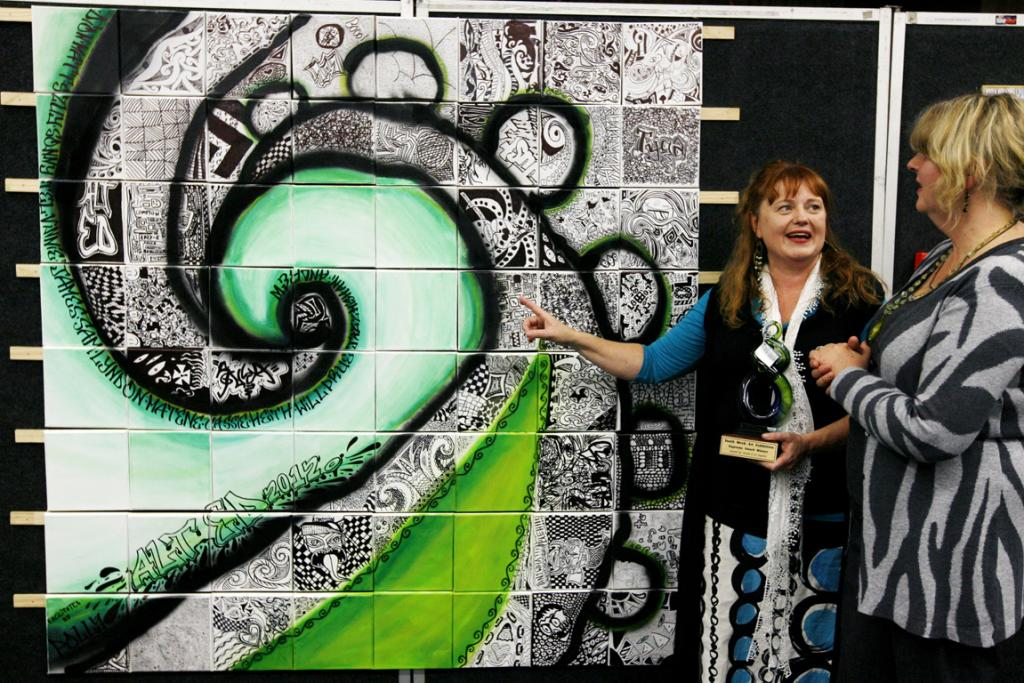 GROUP WORK: Polly Rowe who tutored all 16 Aoraki Alternative Education students that made 'Koru' explains the detail to one of the judges, Annie Lambourne at the Youth Alley art exhibition in the Council Chambers.