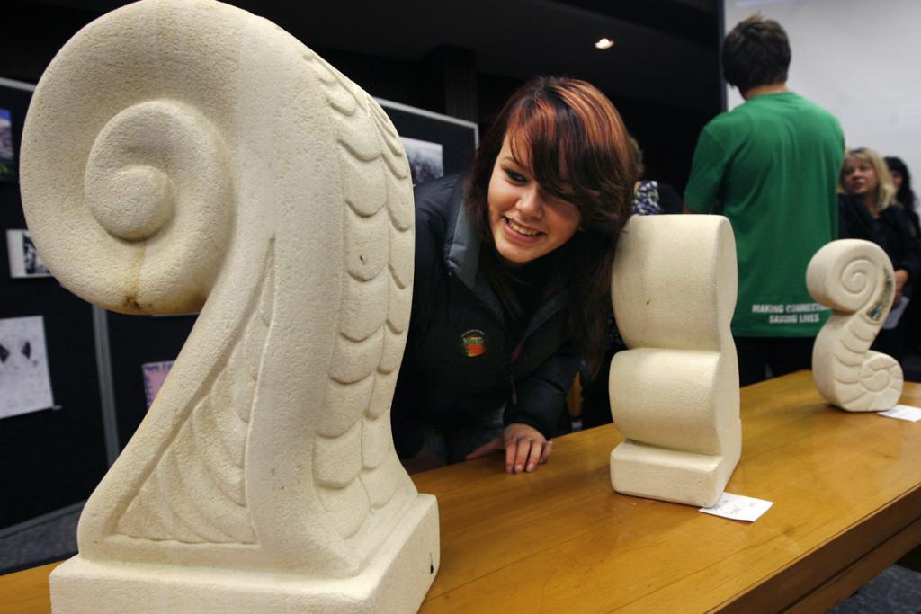 COOL CARVINGS: Hope Maguigan checks out a carving by Ramahi Paea at the Youth Alley art exhibition in the Council Chambers.