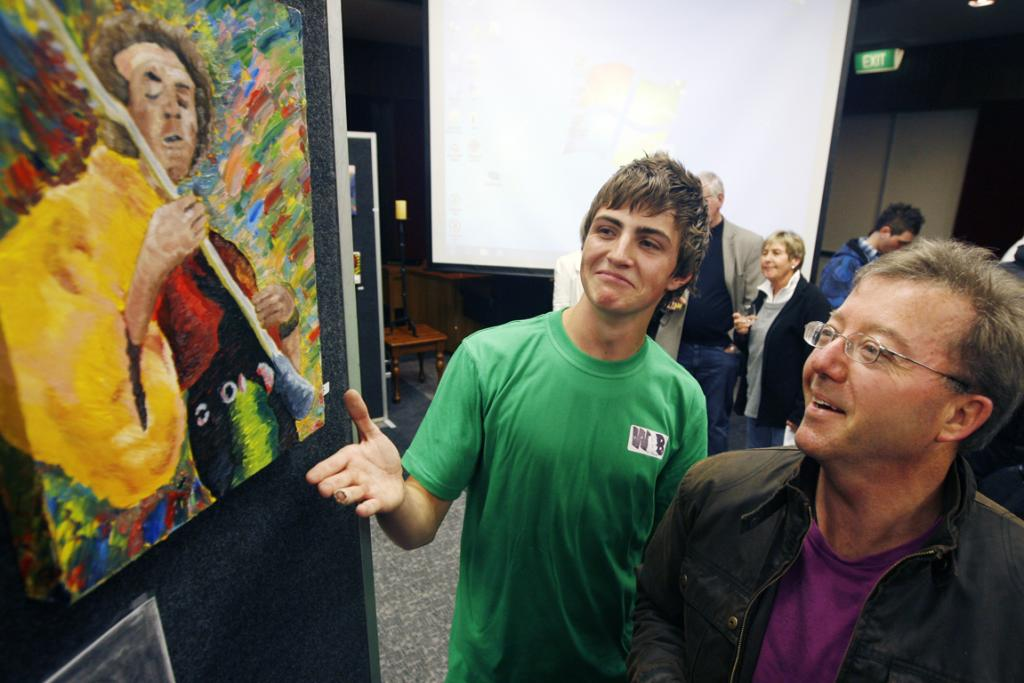 FINISHED PIECE: Reon Chiles shows off his finished artwork of Jimmy Hendrix to his art tutor Wayne Patrick at the Youth Alley art exhibition in the Council Chambers.