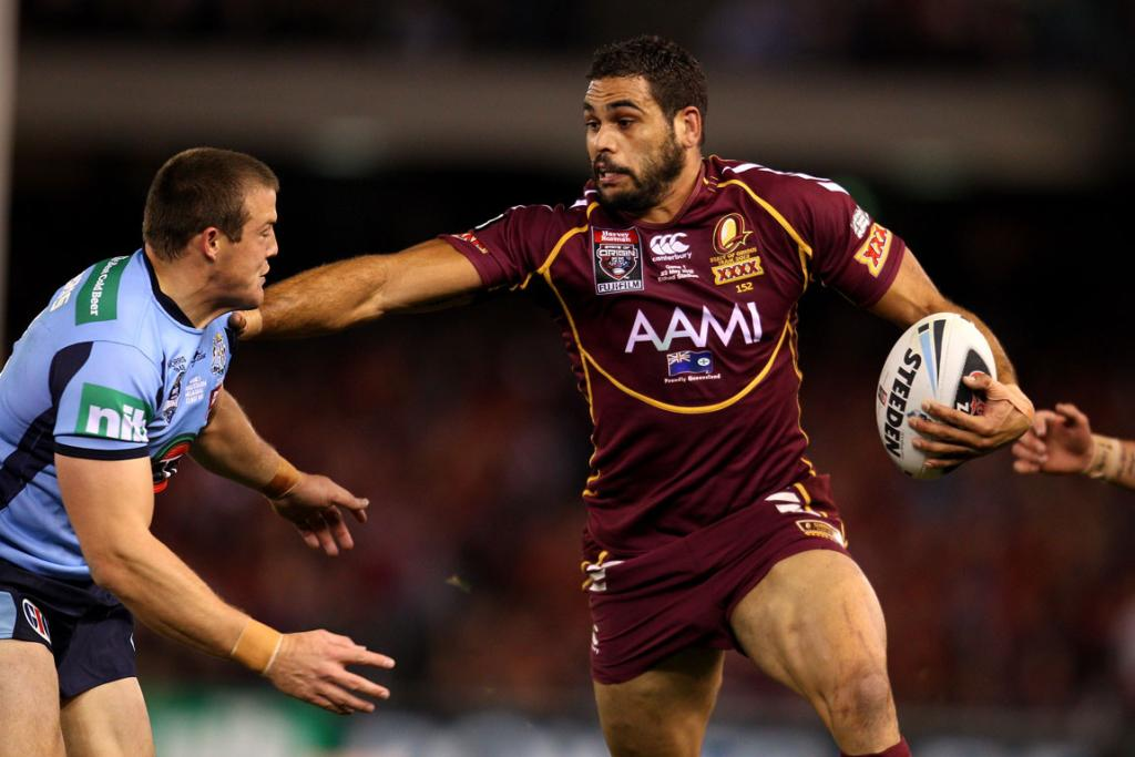 Greg Inglis of the Maroons fends off Josh Morris of the Blues during game one at Etihad Stadium.