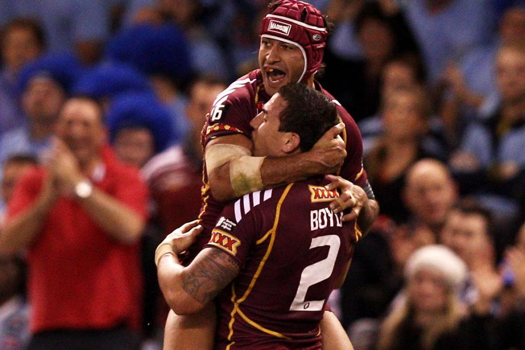 Darius Boyd and Johnathan Thurston of the Maroons celebrate a try during game one at Etihad Stadium.