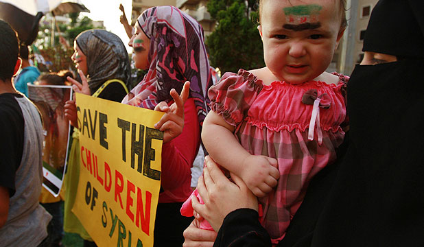 A child with a Syrian opposition flag painted on the face seen at a protest in Lebanon against an attack by government forces on the Syrian city of Houla.