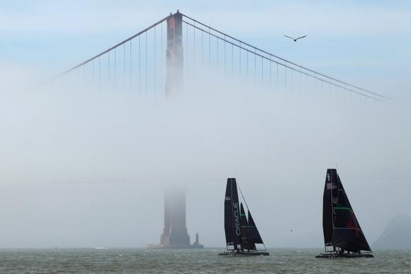 A pair of AC45 yachts from defending America's Cup champion Oracle Racing sails near the South Tower of the Golden Gate Bridge in San Francisco Bay, California, in February, 2012.