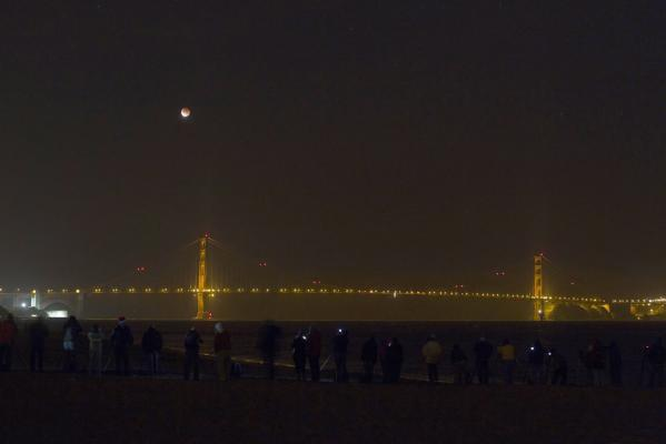 The beginning of a lunar eclipse is seen over the Golden Gate Bridge in San Francisco, California, in December, 2011.