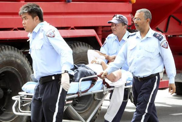 An injured man on a stretcher receives medical attention after a blaze at the Villaggio Mall in Doha's west end.